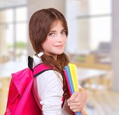 Side view of cute teen girl standing in classroom with colorful books in hands and bright pink backp