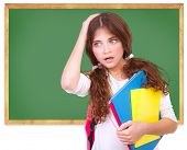 Portrait of confused school girl holding head by hand on green chalkboard background, didn't know an
