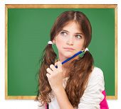 Closeup portrait of cute girl standing near chalkboard and try to remember answer on question, passi