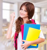 Happy teen girl with hand up in classroom, getting good mark, enjoying education at school, study an