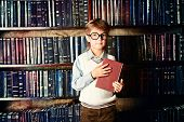 Smart boy stands in the library by the bookshelves with many old books. Educational concept. Science