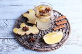 Cup of ginger drink with lemon on wicker mat on wooden background