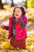 Happy little girl playing in the sunny autumn park