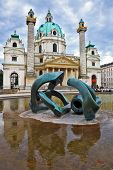 VIENNA, AUSTRIA - SEPTEMBER 26, 2013: Saint Karl Borromey's well-known church in Baroque style. On the square in front of church a big pond with a sculpture the Modernist style