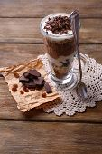 Yogurt, with chocolate cream, chopped chocolate and muesli served in glass on wooden background