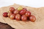 Pink grape on paper on wooden background