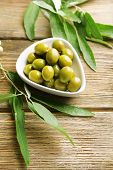 Green olives in bowl with leaves on table close-up