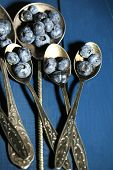 Tasty ripe blueberries in spoons, on wooden background