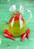 Homemade natural infused olive oil with red chili peppers on color wooden background