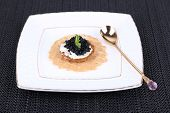 Black caviar with crispy bread on plate on dark fabric background