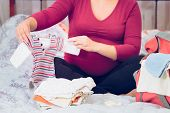 Pregnant Woman Packing Hospital Bag Preparing For Labor