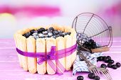 Tasty cake Charlotte with blueberries on wooden table, on light background