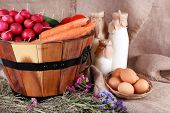 Big round basket with dried grass, vegetables, milk and fresh eggs on sacking background