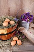Big round basket with dried grass and fresh eggs on sacking background