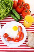 Scrambled eggs with vegetables and juice served on plate on fabric background