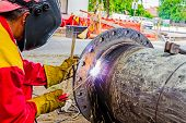 picture of welding  - Welder is welding a pipe in a trench - JPG