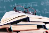Books and glasses on blackboard background