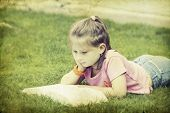 Vintage photo of girl reading a book in the park