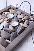 Candles on vintage tray with sea pebbles, on wooden background