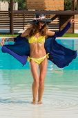 Beautiful young woman at the summer lounge by the swimming pool