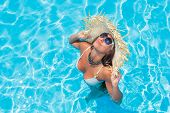 Woman with straw hat and sunglasses in the swimming pool