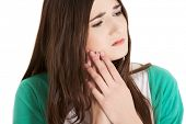 Teen woman pressing her bruised cheek with a painful expression as if she's having a terrible tooth