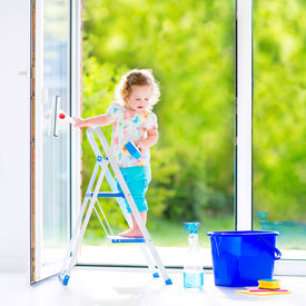 picture of detergent  - Cute laughing curly toddler girl washing a big window with a squeegee in beautiful white living room with door into the garden standing on a ladder next to a blue bucket with water detergent solution spray bottle and sponge - JPG