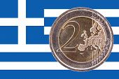 Common Face Of Two Euro Coin On Flag Of Greece