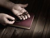 pic of prayer beads  - wooden Christian cross in his palms on the Bible during prayer - JPG