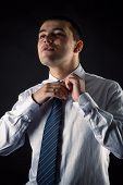 handsome businessman corrects necktie isolated on black