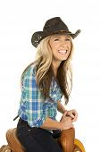picture of cowgirl  - a woman sitting on a saddle in her cowgirl hat with a big smile on her face - JPG