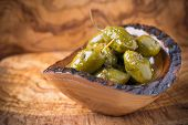 stock photo of kalamata olives  - Green olives marinated with coriander in small wooden bowl over olive wood board selective focus - JPG