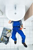 stock photo of plumber  - High Angle View Of Male Plumber Repairing A Sink In Bathroom - JPG