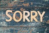 picture of apologize  - Sorry written with wooden letters on rustic blue surface - JPG