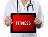 Doctor Showing Tablet With Fitness Text.