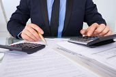 Businessman Calculating Invoices