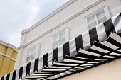 stock photo of marquise  - black and white striped sunblinds building background - JPG