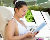 Happy Woman Reading Book On Lounge Chair At Resort