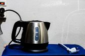 stock photo of boiling water  - Background image of electric kettle with plug on the wall - JPG