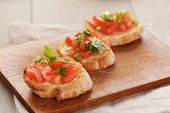 simple italian appetizing bruschetta with tomato and basil, on old table