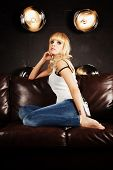 Beautiful Young Woman Sitting On Sofa