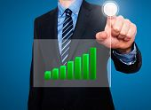 Businessman in dark suit pushing button, visual screen Growth graph.