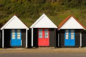 Three colourful beach huts with blue and red doors in a row traditional English structure
