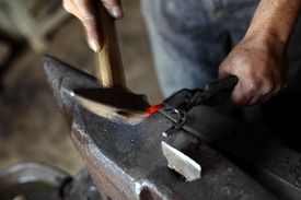 picture of anvil  - Color shot with a blacksmith working on a horse shoe on an anvil - JPG