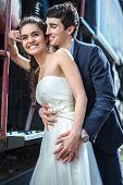 stock photo of locomotive  - Portrait of happy wedding couple near the old steam locomotive - JPG