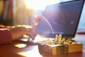 pic of addiction to smoking  - Close up of ashtray full of cigarette with man in background working on laptop computer and smoking indoors on early morning - JPG
