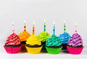 pic of sprinkling  - Rows of colorful cup cakes decorated with birthday candles and sprinkles - JPG