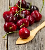 image of spoon  - Close up image freshly picked whole cherries focus on cherry in spoon on rustic wood.