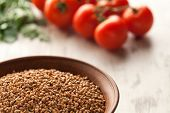 foto of ceramic bowl  - Composition with ceramic bowl dry buckwheat eggs and tomatoes - JPG
