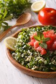 stock photo of tabouleh  - Tabbouleh salad closeup in a wooden bowl and ingredients. vertical ** Note: Shallow depth of field - JPG